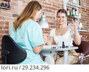 Купить «Manicurist filing and shaping nails to girl in modern beauty salon», фото № 29234296, снято 30 мая 2018 г. (c) Яков Филимонов / Фотобанк Лори