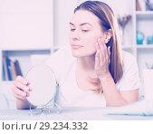 Купить «Cheerful woman is concentrared looking on her face in the mirror», фото № 29234332, снято 29 марта 2018 г. (c) Яков Филимонов / Фотобанк Лори