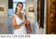 Купить «Woman visiting painting exhibition», фото № 29234404, снято 28 июля 2018 г. (c) Яков Филимонов / Фотобанк Лори