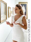Купить «Woman visiting painting exhibition», фото № 29234428, снято 28 июля 2018 г. (c) Яков Филимонов / Фотобанк Лори