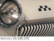 Купить «Fragment of the front part of a vintage taxi car, focus on the checker emblem and radiator, headlight is in blur», фото № 29240376, снято 13 октября 2018 г. (c) Евгений Харитонов / Фотобанк Лори