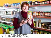 Купить «Woman in shop holding preserves», фото № 29240772, снято 15 декабря 2017 г. (c) Яков Филимонов / Фотобанк Лори