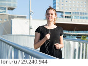 Купить «Young girl running and listening music on city bridge», фото № 29240944, снято 5 июля 2017 г. (c) Яков Филимонов / Фотобанк Лори