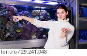 Купить «Young smiling girl near big aquarium is pointing to interesting», фото № 29241048, снято 17 февраля 2017 г. (c) Яков Филимонов / Фотобанк Лори