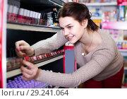 Купить «female customer looking for nail polish in cosmetics shop», фото № 29241064, снято 21 февраля 2017 г. (c) Яков Филимонов / Фотобанк Лори