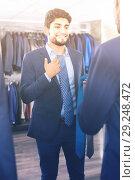 Купить «Customer male is picking up tie for jacket in front of the mirror», фото № 29248472, снято 20 июня 2017 г. (c) Яков Филимонов / Фотобанк Лори