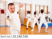 Купить «Sporty young man fencer practicing effective fencing techniques», фото № 29248540, снято 11 июля 2018 г. (c) Яков Филимонов / Фотобанк Лори