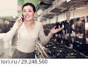 Купить «Woman with phone choosing hob in store», фото № 29248560, снято 21 февраля 2018 г. (c) Яков Филимонов / Фотобанк Лори