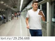 Купить «Man using his phone on subway station», фото № 29256688, снято 24 августа 2018 г. (c) Яков Филимонов / Фотобанк Лори