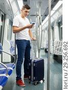 Купить «Man traveling on subway and using smartphone», фото № 29256692, снято 24 августа 2018 г. (c) Яков Филимонов / Фотобанк Лори