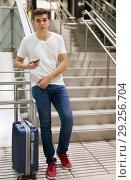 Купить «Man with luggage and phone on stairs», фото № 29256704, снято 24 августа 2018 г. (c) Яков Филимонов / Фотобанк Лори