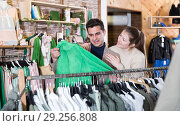 Купить «Smiling woman and man are choosing clothes and looking on green jacket», фото № 29256808, снято 12 марта 2018 г. (c) Яков Филимонов / Фотобанк Лори