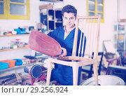 Купить «Craftsman repairing chair in workshop», фото № 29256924, снято 8 апреля 2017 г. (c) Яков Филимонов / Фотобанк Лори