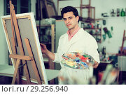 Man near easel painting on canvas. Стоковое фото, фотограф Яков Филимонов / Фотобанк Лори