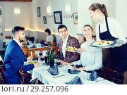 Купить «Polite smiling waitress bringing ordered dishes to guests at restaurant», фото № 29257096, снято 7 ноября 2017 г. (c) Яков Филимонов / Фотобанк Лори