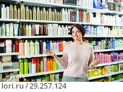 Купить «Positive glad woman choosing hair care products», фото № 29257124, снято 20 июля 2019 г. (c) Яков Филимонов / Фотобанк Лори