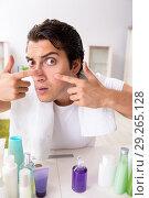 Купить «Young handsome man in the bathroom in hygiene concept», фото № 29265128, снято 19 июля 2018 г. (c) Elnur / Фотобанк Лори