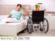 Купить «Young handsome disabled man recovering at home», фото № 29266156, снято 28 июня 2018 г. (c) Elnur / Фотобанк Лори