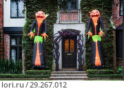 Купить «The house is decorated for Halloween: Two huge inflatable monsters with pumpkin heads stand at the entrance to the house. Night, Houston, Texas, United States», фото № 29267012, снято 18 октября 2018 г. (c) Ирина Кожемякина / Фотобанк Лори