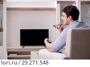 Купить «Young man watching tv at home», фото № 29271548, снято 9 марта 2018 г. (c) Elnur / Фотобанк Лори
