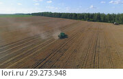Купить «Aerial view of combine harvester on wheat field. Tracking the subject in the center of the frame.», видеоролик № 29273948, снято 14 сентября 2018 г. (c) Андрей Радченко / Фотобанк Лори