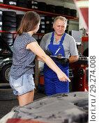 Купить «Mechanic with female client», фото № 29274008, снято 4 сентября 2018 г. (c) Яков Филимонов / Фотобанк Лори