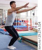 Купить «Man doing acrobatics exercises», фото № 29274324, снято 18 июля 2018 г. (c) Яков Филимонов / Фотобанк Лори