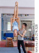 Купить «Man and woman doing acrobatic exercises in gym», фото № 29274328, снято 18 июля 2018 г. (c) Яков Филимонов / Фотобанк Лори