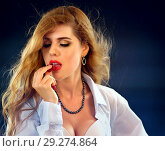 Купить «Woman eating berry. Pin up girl wearing unbuttoned blouse and bra.», фото № 29274864, снято 18 ноября 2018 г. (c) Gennadiy Poznyakov / Фотобанк Лори