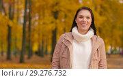 Купить «happy young woman walking in autumn park», видеоролик № 29276732, снято 18 октября 2018 г. (c) Syda Productions / Фотобанк Лори