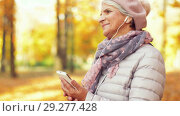 Купить «old woman with smartphone and earphones in autumn», видеоролик № 29277428, снято 22 октября 2018 г. (c) Syda Productions / Фотобанк Лори