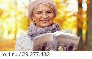 Купить «senior woman with city guide at autumn park», видеоролик № 29277432, снято 22 октября 2018 г. (c) Syda Productions / Фотобанк Лори