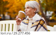 Купить «senior woman drinking coffee in autumn park», видеоролик № 29277456, снято 22 октября 2018 г. (c) Syda Productions / Фотобанк Лори