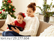 Купить «mother and daughter with tablet pc on christmas», фото № 29277604, снято 29 августа 2018 г. (c) Syda Productions / Фотобанк Лори