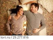 Купить «happy couple with garland lying on floor at home», фото № 29277816, снято 13 января 2018 г. (c) Syda Productions / Фотобанк Лори