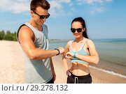 Купить «happy couple with fitness trackers on summer beach», фото № 29278132, снято 1 августа 2018 г. (c) Syda Productions / Фотобанк Лори