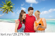 Купить «friends with smartphone over beach background», фото № 29279708, снято 30 июня 2018 г. (c) Syda Productions / Фотобанк Лори