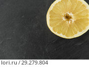 Купить «close up of lemon slice on slate table top», фото № 29279804, снято 4 апреля 2018 г. (c) Syda Productions / Фотобанк Лори