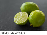 Купить «close up of limes on slate table top», фото № 29279816, снято 4 апреля 2018 г. (c) Syda Productions / Фотобанк Лори