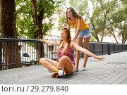 Купить «teenage girls riding skateboard on city street», фото № 29279840, снято 19 июля 2018 г. (c) Syda Productions / Фотобанк Лори