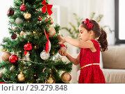 Купить «little girl decorating christmas tree at home», фото № 29279848, снято 29 августа 2018 г. (c) Syda Productions / Фотобанк Лори