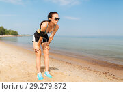 Купить «female runner with earphones and arm band on beach», фото № 29279872, снято 1 августа 2018 г. (c) Syda Productions / Фотобанк Лори