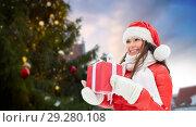 Купить «happy woman with gift over christmas tree», фото № 29280108, снято 7 января 2017 г. (c) Syda Productions / Фотобанк Лори