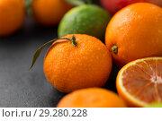 Купить «close up of citrus fruits on stone table», фото № 29280228, снято 4 апреля 2018 г. (c) Syda Productions / Фотобанк Лори