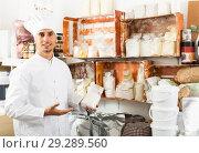 Купить «cook taking package with grit in pantry room», фото № 29289560, снято 15 ноября 2018 г. (c) Яков Филимонов / Фотобанк Лори