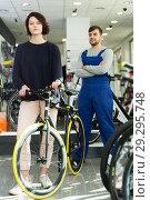 Купить «man seller and woman standing in bicycle store», фото № 29295748, снято 8 января 2018 г. (c) Яков Филимонов / Фотобанк Лори