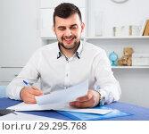 Купить «Smiling young man signing profitable financial agreement», фото № 29295768, снято 5 марта 2017 г. (c) Яков Филимонов / Фотобанк Лори