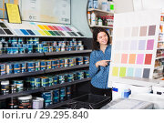 Купить «young female customer examining color scheme variants in paint store», фото № 29295840, снято 9 марта 2017 г. (c) Яков Филимонов / Фотобанк Лори