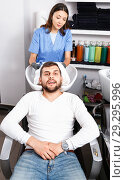 Купить «Portrait of woman hairdresser in gloves washing hair of smiling man in salon», фото № 29295996, снято 25 апреля 2018 г. (c) Яков Филимонов / Фотобанк Лори