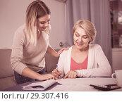 Купить «Daughter helps mother to lead home accounting», фото № 29307416, снято 13 ноября 2017 г. (c) Яков Филимонов / Фотобанк Лори